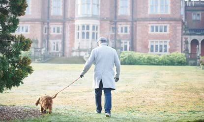 man with dog on lead with crewe hall in background